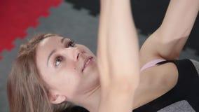 La pesa de gimnasia atlética hermosa de la chica joven ejercita los músculos pectorales en el gimnasio almacen de metraje de vídeo