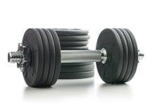 La pesa de gimnasia y los pesos del metal foto de archivo