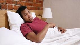 La pesadilla, hombre africano durmiente se despierta en choque por sueño asustadizo almacen de metraje de vídeo