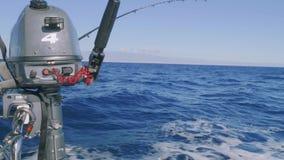La pesca con cebo de cuchara con cebo de cuchara de pescados de la ejecución del motor externo en el yate sialing sube almacen de video
