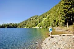 La pesca de la mujer y del perro en un lago apuntala imagenes de archivo
