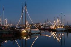 La pesca de madera tradicional iluminada envía en la noche en puerto holandés imagen de archivo libre de regalías