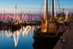 La pesca de madera tradicional iluminada envía en la noche en puerto holandés imagen de archivo