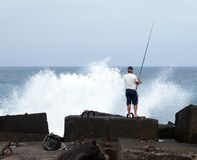 La pesca de un más viejo hombre en el mar se colocaba en rocas con las ondas dramáticas a Foto de archivo libre de regalías
