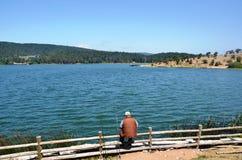 La pesca dell'uomo alla riva del lago Fotografia Stock