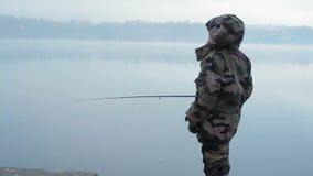 La pescadora de la muchacha en capturas del traje del camuflaje pesca en una barra la mañana en el río brumoso del otoño metrajes