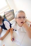 La petite écolière d'une école primaire s'assied à un bureau dans l'attention Photographie stock libre de droits