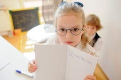 La petite écolière mignonne en verres montre son cahier photo stock