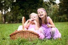 La petite amie deux mignonne dans de belles robes rient dans la somme Photo libre de droits