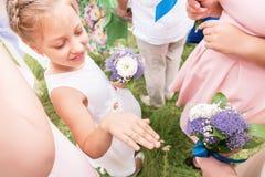 La petite amie douce de la jeune mariée vante ses anneaux aux amies adultes Image libre de droits