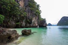 La petite baie entourée par la chaux complexe, la plage blanche molle de sable et l'émeraude colorent la mer à l'île d'islandPara Photos stock