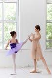La petite ballerine posant au barre de ballet avec photographie stock libre de droits
