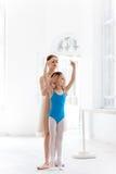 La petite ballerine posant au barre de ballet avec le professeur personnel dans le studio de danse photographie stock