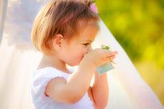 La petite belle fille dans une robe blanche boit d'une tasse images libres de droits
