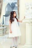 La petite brune mignonne regarde la statue dans le restaurant Photographie stock libre de droits