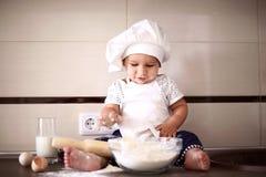 La petite chéri mignonne dans un capuchon de cuisinier rit Photographie stock libre de droits