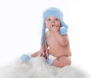 La petite chéri mignonne est regardante et utilisante le chapeau bleu Photographie stock