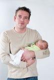 La petite chéri nouveau-née beeing s'est retenue par son père Image stock