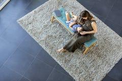 La petite configuration de fille sur son recouvrement du ` s de mère et apprécient, regardent de l'abo photographie stock libre de droits