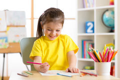 La petite couleur de dessin mignonne de fille d'enfant d'élève du cours préparatoire crayonne à la maison ou studio Photographie stock