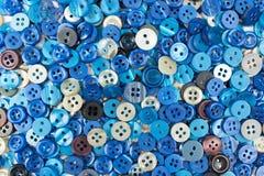 La petite couture bleue se boutonne sur un fond blanc Photographie stock