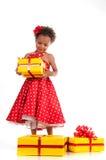 La petite dame en rouge a pointillé la robe avec les boîte-cadeau jaunes Anniversaire, nouvelle année Image stock