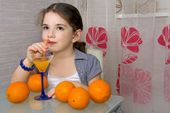 La petite fille à la table boit du jus d'orange par un tube Photo libre de droits