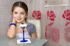 La petite fille à la table mange la crême glacée Photographie stock