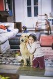 La petite fille à la maison avec son chien de golden retriever ont l'affection Images stock