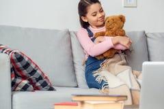 La petite fille à la maison s'asseyant étreignant l'ours de nounours a détendu photos libres de droits