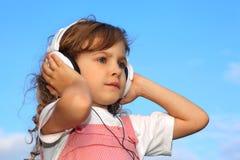 La petite fille écoute la musique par des écouteurs Images stock