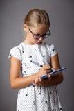 La petite fille écrit avec la Tablette Photos stock