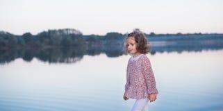 La petite fille élégante marche sur la banque du lac Un beau portrait de la fille photos stock