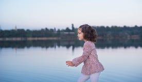 La petite fille élégante marche sur la banque du lac Un beau portrait de la fille photos libres de droits