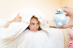 La petite fille étant a été réveillée par le réveil Photo stock