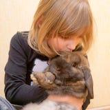 La petite fille étreignant et embrassant le lapin. Photographie stock libre de droits