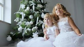 La petite fille étreint la soeur et sourit avec la neige artificielle sur des cheveux sur l'arbre de Noël de fond avec des orneme banque de vidéos