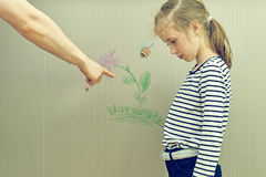 La petite fille a abîmé le papier peint Image libre de droits