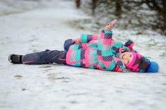 La petite fille a abaissé d'une colline et se trouve sur la neige image libre de droits