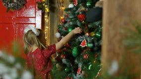 La petite fille accrochant sur l'arbre de Noël joue Photos stock
