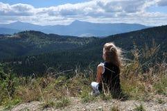 La petite fille admire le paysage de montagne photographie stock