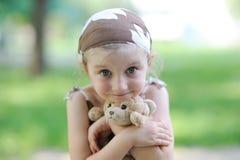 La petite fille adorable étreint son jouet Photos stock