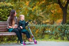 La petite fille adorable avec la maman apprécient le jour d'automne en parc d'automne dehors Photographie stock