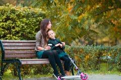 La petite fille adorable avec la maman apprécient le jour d'automne en parc d'automne dehors Photo stock