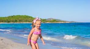 La petite fille adorable ont l'amusement en eau peu profonde à Photo libre de droits