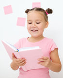 La petite fille affiche un livre Photo stock
