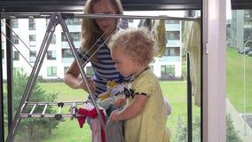 La petite fille aidant sa femme de mère à accrocher a lavé la blanchisserie clips vidéos