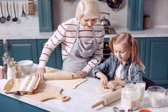 La petite fille aidant sa grand-mère font des biscuits Photo stock