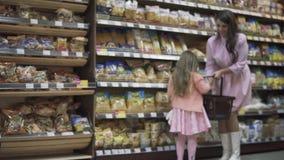 La petite fille aide des achats de maman au supermarché banque de vidéos