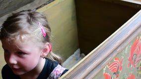 La petite fille apparaît dans un coffre de vintage la petite fille que mignonne ouvre le coffre de vintage de l'intérieur Enfance banque de vidéos